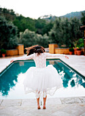 Bride diving into swimming pool