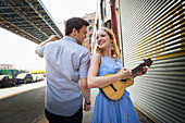 Caucasian couple playing ukulele in city
