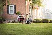 Caucasian family eating in backyard