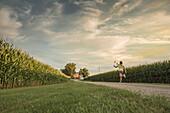 Caucasian girl walking on dirt path by corn field