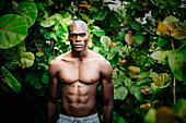 Black man standing in lush garden