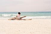Woman sunbathing on driftwood log on beach