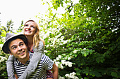Caucasian man carrying girlfriend piggyback in garden