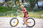 Hispanic woman riding bicycle on beach