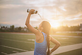 Mixed race athlete pouring water bottle on herself on sports field