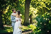 Caucasian bride and groom hugging on rural road