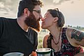 Caucasian couple kissing at picnic table