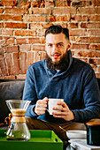 Man drinking coffee on sofa in living room