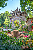 Traditional Chinese stone gate, a place to rest amidst lush vegetation and floral decorations at Wansong Academy, Hangzhou, Zhejiang, China, Asia