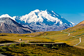 Scenic view of Mt. McKinley, Thorofare Pass, and Stony Dome in the foreground with a vehicle on the park road, Denali National Park, Interior Alaska