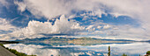 Scenic view of mountains and clouds reflecting in the calm waters of Kluane Lake, Yukon Territory, Canada, Summer