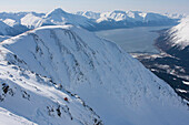 Downhill Skier On Max's Mountain Overlooking Girdwood And The Turnagain Arm And Kenai Mountains, Southcentral Alaska, Winter