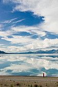 A woman stands at the shore of Kluane Lake with mountains and clouds reflecting in the calm waters of Kluane Lake, Yukon Territory, Canada, Summer