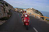 Young couple riding a red Vespa scooter on a coastal road along the Cap de Formentor peninsula with Faro de Formentor lighthouse behind, Palma, Mallorca, Balearic Islands, Spain