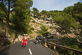 Young couple riding a red Vespa scooter on a coastal road along the Cap de Formentor peninsula, group of cyclists riding in the other direction, Palma, Mallorca, Balearic Islands, Spain