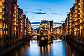 Blick in der Abenddaemmerung auf das Wasserschloss in der alten Speicherstadt, Hafencity Hamburg, Norddeutschland, Deutschland