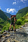 Young woman crosses a stream on the Annapurna Circuit Trek in the Marsyangdi valley, Nepal, Himalaya, Asia