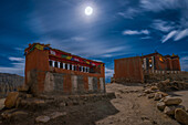 Full moon above the monastery, gompa and prayer wheels in Tsarang, Charang, tibetian village with a buddhist Gompa at the Kali Gandaki valley, the deepest valley in the world, fertile fields are only possible in the high desert due to a elaborate irrigati