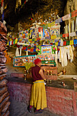 Monch at the altar of the Ranchung Cave, Buddhist monastery, cave temple, gompa with prayer flags, near Samar, Kingdom of Mustang, Nepal, Himalaya, Asia