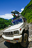 Man sitting an the roof of a 4x4 vehicle, jeep with an umbrella in the Marsyangdi-valley, Nepal, Himalaya, Asia