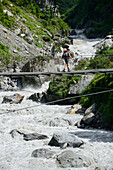 Young woman crossing the Marsyangdi river on the Annapurna Circuit Trek in the Marsyangdi valley, Nepal, Himalaya, Asia