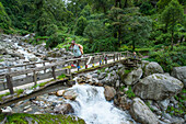 Man crossing a river on a wooden bridge on the Annapurna Circuit Trek in the Marsyangdi valley, Nepal, Himalaya, Asia