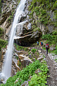 Two young women and a young man walking behind a waterfall on the Nar Phu Trek, Nepal, Himalaya, Asia