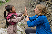 Young woman playing with a small girl in Nar on the Nar Phu Trek, Nepal, Himalaya, Asia