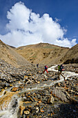 A young woman and a young man jumping over a stream on the way from Nar over Teri Tal to Mustang, Nepal, Himalaya, Asia