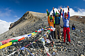 Four hikers, trekkers at Teri La Pass (5595 m) with buddhist prayer flags, on their way from Nar over Teri Tal to Mustang, Nepal, Himalaya, Asia