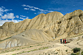 Three trekkers, hikers in the surreal landscape typical for Mustang in the high desert around the Kali Gandaki valley, the deepest valley in the world, Mustang, Nepal, Himalaya, Asia