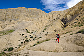 Young woman, hiker, trekker in the surreal landscape typical for Mustang in the high desert around the Kali Gandaki valley, the deepest valley in the world, Mustang, Nepal, Himalaya, Asia
