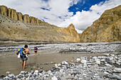 Two young men, hiker, trekker crossing the river Dhechyang Khola in the surreal landscape typical for Mustang in the high desert around the Kali Gandaki valley, the deepest valley in the world, Mustang, Nepal, Himalaya, Asia