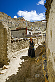 Tibetan woman in Gara, Yara on 4600 m, tibetian village with a buddhist Gompa at the Kali Gandaki valley, the deepest valley in the world, fertile fields are only possible in the high desert due to a elaborate irrigation system, Mustang, Nepal, Himalaya