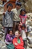 Young women, trekker, hiker with local children at Luri Gompa, Luri Gumba, Buddhist monastery, cave temple, near Yara, Gara, Kingdom of Mustang, Nepal, Himalaya, Asia