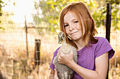 Girl holding duck on farm