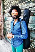 Mixed race musician carrying guitar outdoors