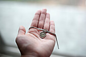 Hand of Caucasian woman holding necklace
