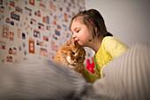 Caucasian girl hugging cat on bed