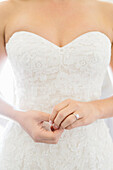 Close up of bride wearing wedding dress and engagement ring