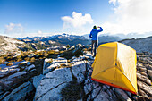 A young woman enjoys the view from her campsite on a rocky mountain ridge.