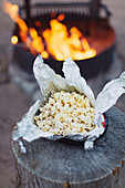 Popcorn in an aluminium foil keeps on a heater on a wood log to fry.