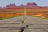 The road that leads to Monument Valley Navajo Tribal Park curves down and then back up again as it approaches the sandstone sculptures that make up the park in Mexican Hat, Utah