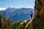 hiking woman in mountain forest, Mixed forest, fall, view from Kramer on Alpspitze and Wetrerstein mountains, Garmisch, Garmisch, Upper Bavaria, Alps, Germany, Europe