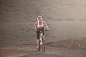 A blonde girl rides her bike uphill on a rocky place in Fuerteventura, canary islands
