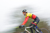 Blurred/Motion image of a male cyclocross racer at speed riding through a row or trees in a race.