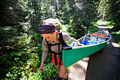 A young woman portages her canoe during a canoe trip through Bowron Lake Provincial Park.