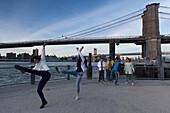 Dancers underneath Brooklyn Bridge, Manhattan, New York, USA
