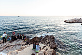 Young people sitting on rocks along the Adriatic coast, Rovinj, Istria, Croatia