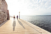 Two men walking along the waterfront of Porec, Istria, Croatia